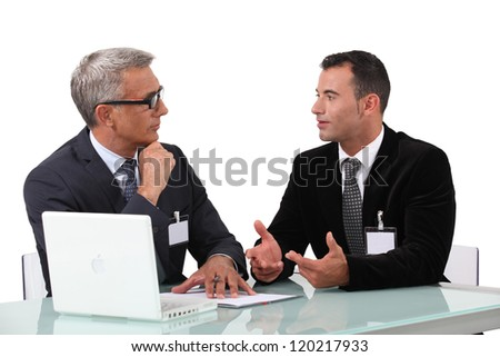 Men chatting at a desk - stock photo