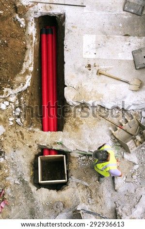 men construction workers working  to repair  the water, fiber optic and sewer pipes in the  city at street - stock photo