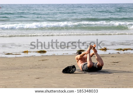 Men doing Yoga exercises on the beach/Yoga Bowl Pose/ San Diego, California - stock photo