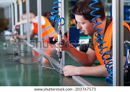 Men during precision work on production line, horizontal - stock photo