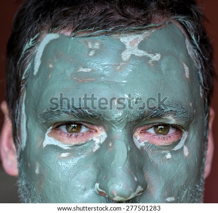 Men face closeup on facial blue clay mask. Treatment and care for the face skin - stock photo