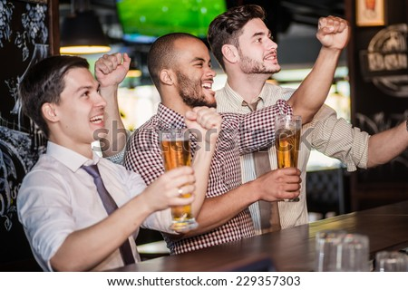 Men fans waving their hands and watching football on TV and drink beer. Three other men drinking beer and having fun together in the bar while there is a football game on TV - stock photo