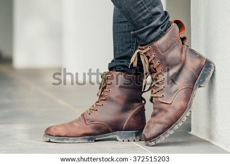 Men fashion, brown leather boots and blue jeans  - stock photo