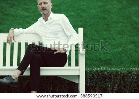 Men fashion concept. Portrait of mature charismatic man with blue eyes and beard wearing white shirt and black pants sitting on bench. Silver short hair. Iconic classic style. Copy-space. Outdoor shot - stock photo