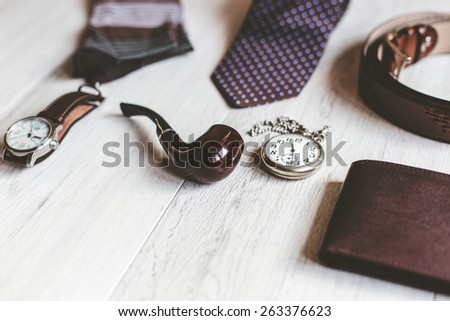 Men fashion. Men accessories. Men socks, wallet, belt, pocket watch, watch, tie and smoking pipe. Still life. Business look.  - stock photo