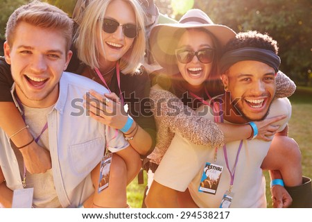 Men Giving Woman Piggybacks On Their Way To Music Festival - stock photo