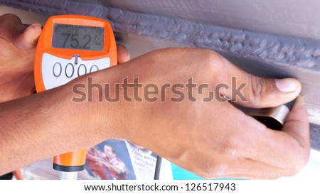 Men hand held the dry film thickness gauge to check the coating thickness. - stock photo