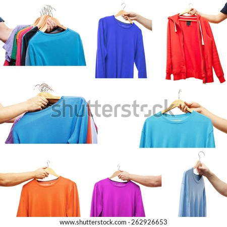 men hand holding hangers with sweaters and t-shirts - stock photo