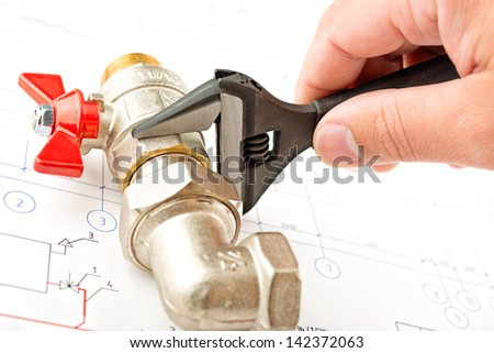 Men hands with spanner bind a faucet - stock photo
