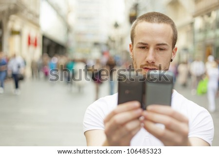 Men holding in hands two mobile phone, blurred city street and people in background - stock photo