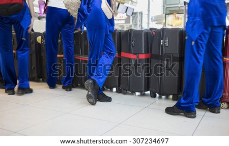 Men in performing clothes with suitcase at airport. Concept of artist travelling by airway  - stock photo