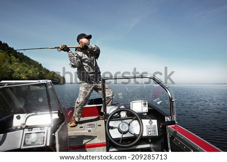 Men is fishing at the boat - stock photo