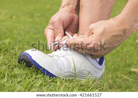 Men is tying shoes laces for jogging at park. - stock photo