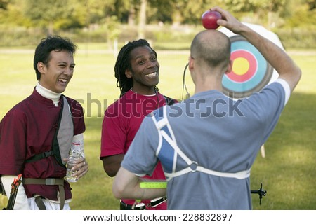 Men joking with one man holding an apple on his head - stock photo
