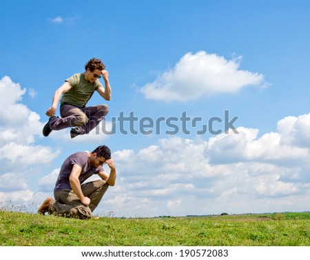 Men jumping one over another and fluffy clouds in background  - stock photo