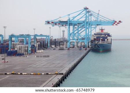 Men load big cargo boat docked to industrial port with blue cranes - stock photo