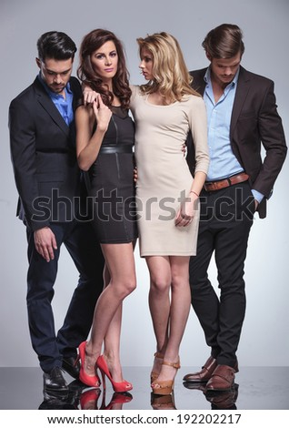 men looking down while standing next to their girlfriends in studio - stock photo