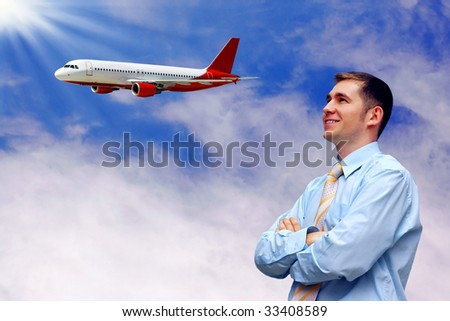 men looks at airplane in air with blue sky - stock photo