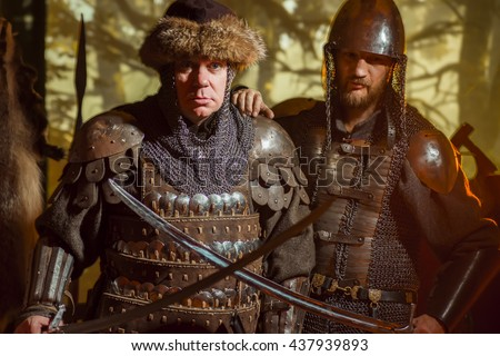 Men medieval knights in armor, blurred motion. Retro medieval background. - stock photo