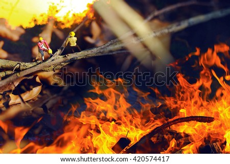 Men(miniature) working with wildfire.Deforestation. - stock photo