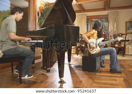 Men playing guitar and piano - stock photo