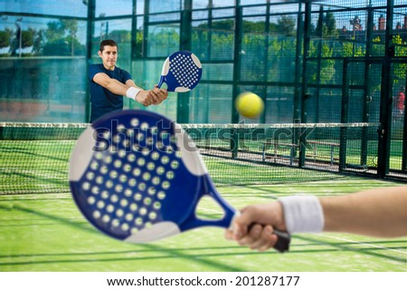 men playing paddle tennis standing and swatting the ball on court - stock photo