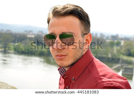 Men posing outside in formal red shirt with sun glasses - stock photo