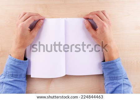 Men reading empty open book on wooden table background - stock photo
