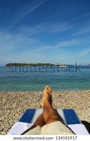 Men relaxing by sea in rocky beach - stock photo