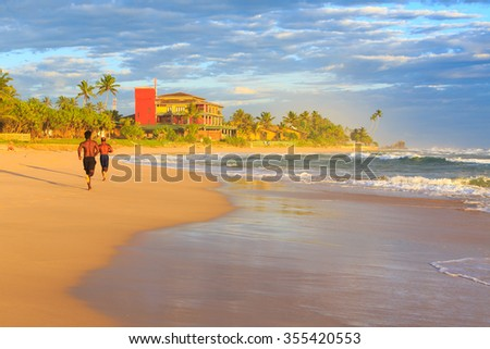 Men running on the beach at sunset on a tropical island - stock photo