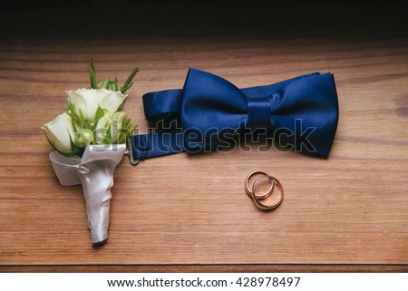 Men's accessories - bow tie, wedding rings on background. - stock photo
