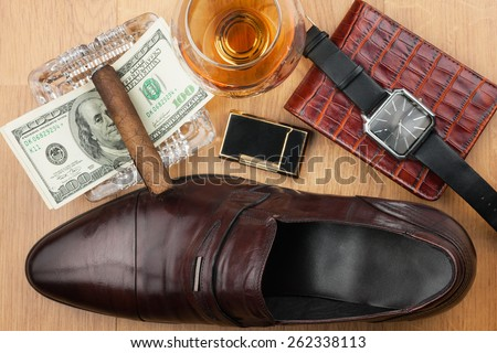 Men's accessories, cigar, ashtray, lighter, money, shoe, glass  on  wooden floor, can be used as background - stock photo