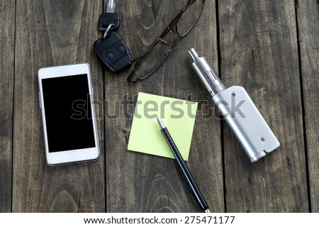 Men's Accessories , top view on a wooden background,  contains the phone , key, pen, glasses  and e-cigarette - stock photo