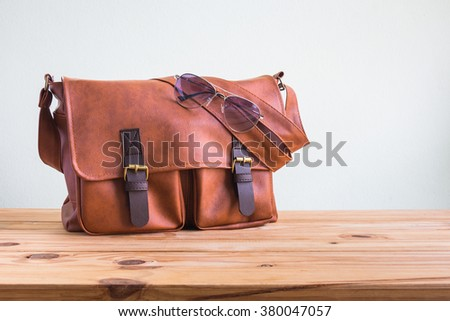 Men's accessories with brown leather bags and sunglasses on wooden table over wall background - stock photo