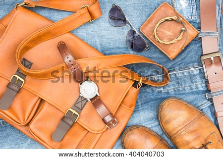 Men's accessories with brown leather bags, old boots and blue jeans background - stock photo