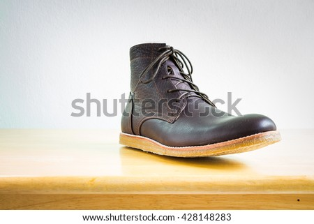Men's accessories with brown leather boots on wooden table, bar or counter over gray wall background - stock photo