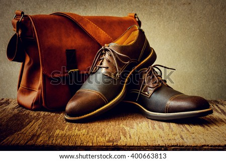 Men's accessories with brown shoes, leather bag and belt on wooden table over grunge background, still life style - stock photo