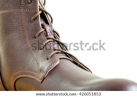 Men's accessories with close-up brown leather boots with copy space on white wall background - stock photo