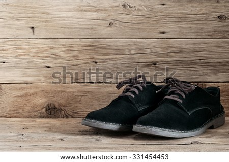 Men's black suede boots with laces on wooden background close up - stock photo