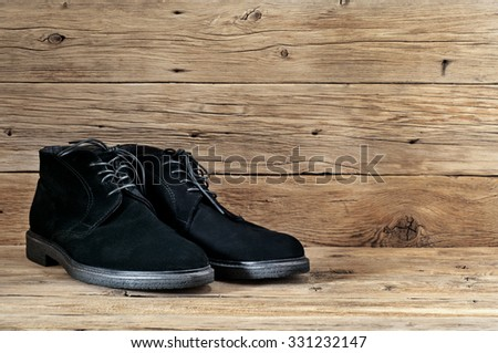 Men's black suede boots with laces on wooden background closeup - stock photo