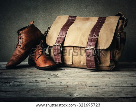 Men's boots and brown bag on wooden table over wall grunge background - stock photo