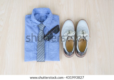 Men's casual, blue shirt with necktie, sunglasses and vintage man's shoes on wood background. Travel to work concept. - stock photo