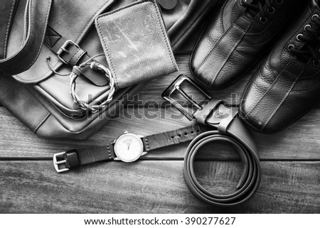 Men's casual outfits with leather accessories on wooden background, black and white - stock photo