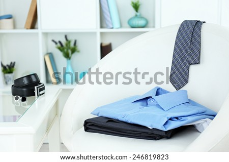 Men's clothes on chair with shelf on background - stock photo