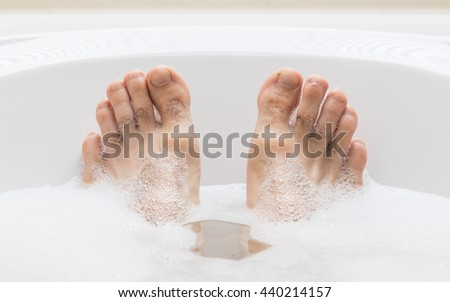 Men's feet in a bright white bathtub, selective focus on toes - stock photo