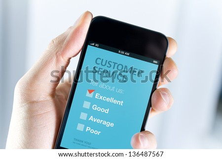 Men's hand holding modern mobile phone with customer service survey form on a screen. Red tick on excellent choice showing customer satisfaction. - stock photo
