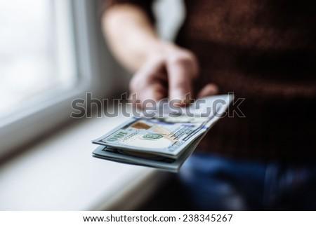 Men's hand holding money american hundred dollar bills. Hand of business man offering money. - stock photo