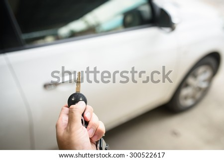 Men's hand presses on the remote control car lock systems - stock photo