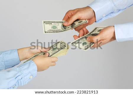 Men's hands give money american hundred dollar bills to boy hands. Businessman give money to business boy. Father and son.  - stock photo
