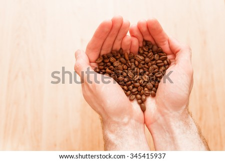men's hands holding coffee beans in the shape of a heart - stock photo
